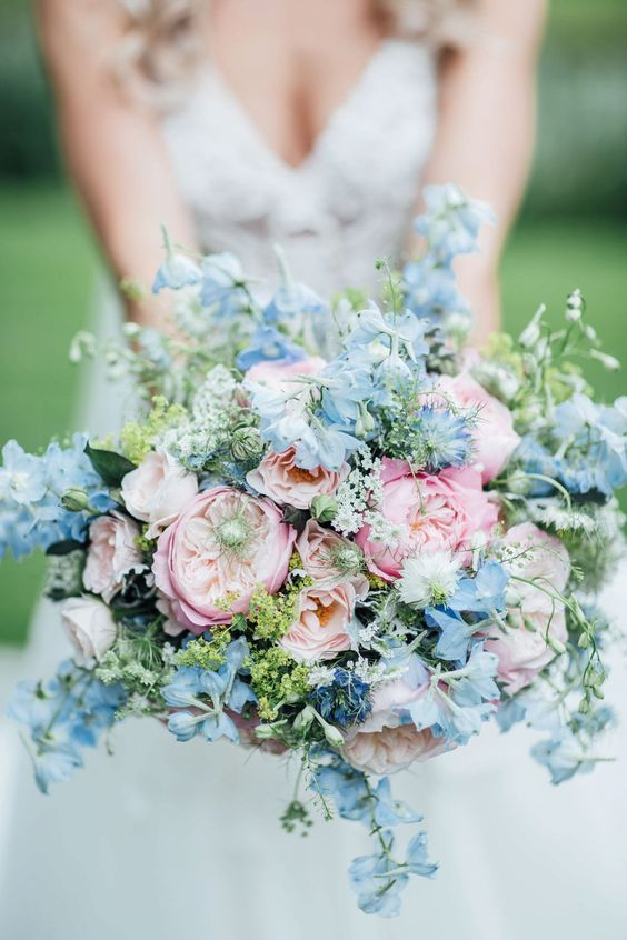 a pastel wedding bouquet with blush, pink and pastel blue blooms and greenery