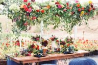 24 a super lush greenery and bright bloom decoration over the reception table for a bright boho wedding