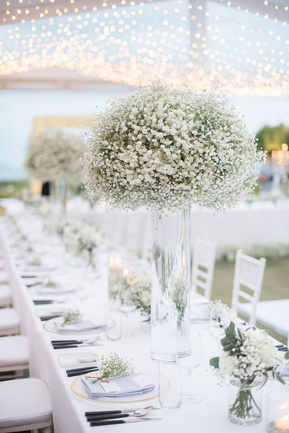 a chic white wedding tablescape with white blooms, some greenery and touches of gold plus black cutlery