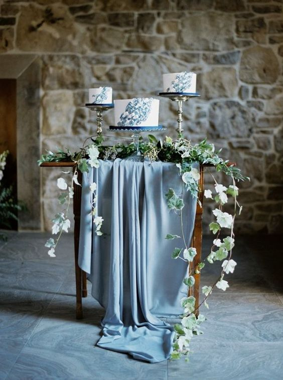 a sweets table with a pastel blue tablecloth, greenery and three wedding cakes with blue brushstrokes