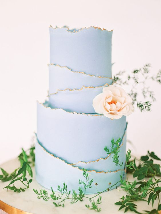 a pastel blue wedding cake with a raw gilded edge and a blush bloom for decor