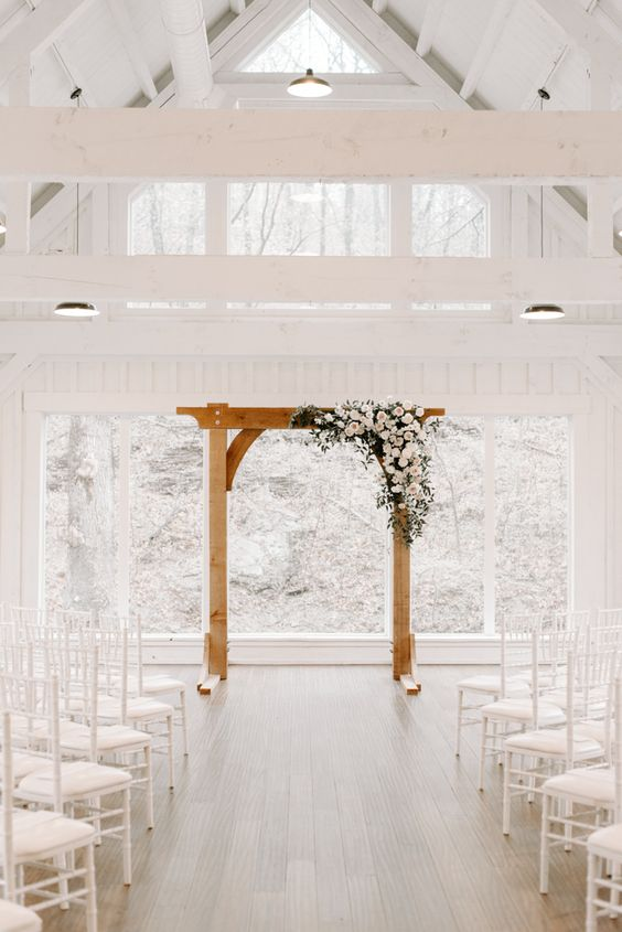 a pure white wedding ceremony space with white chairs and a wooden frame decorated with blush and white blooms