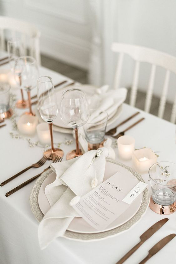 an all-neutral and chic wedding tablescape with candles, brass and copper touches and textural matte plates