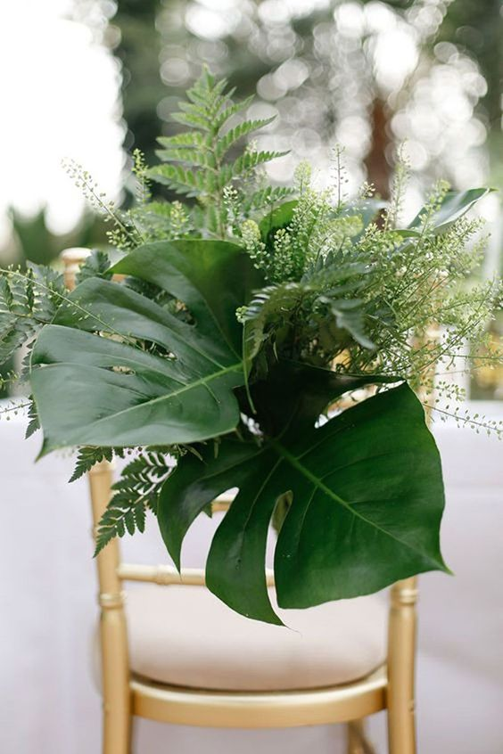 wedding chair decor with lush tropical leaves and greenery plus some light blooms
