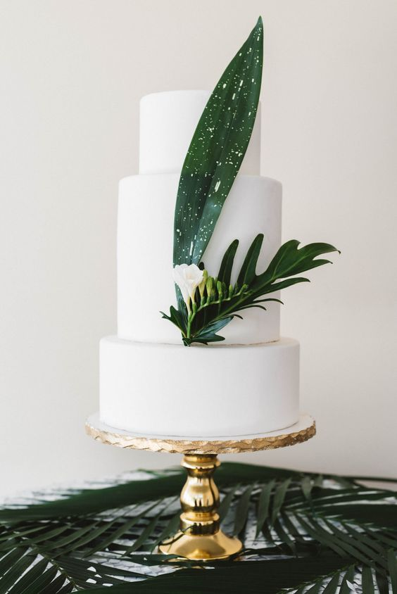 a white wedding cake decorated with tropical leaves and a single white bloom for a beach or tropical wedding