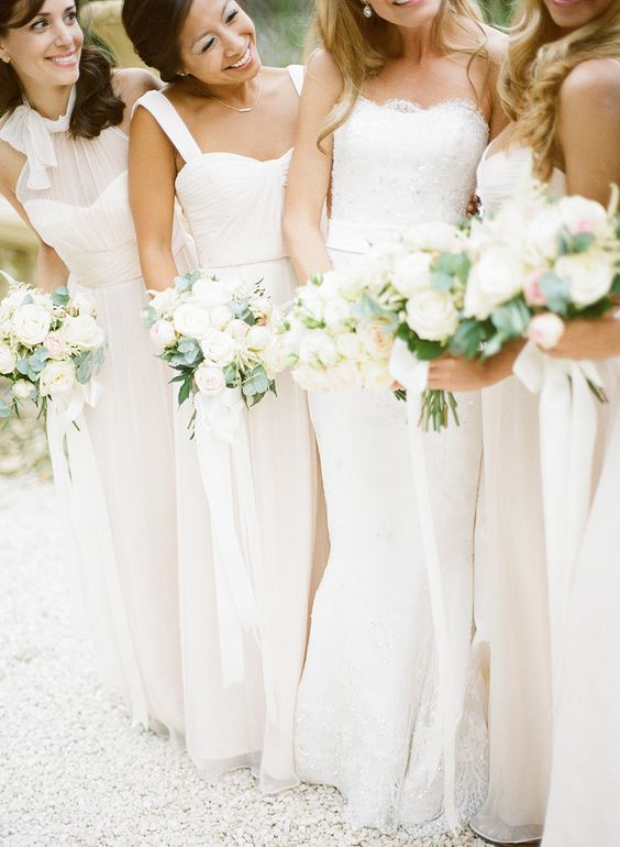 mismatching bridesmaid dresses and neutral bouquets for a chic all-white bridal party look