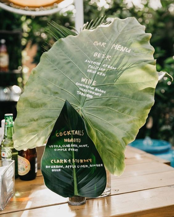 a bar wedding menu done on two large leaves is a very creative idea for a tropical wedding