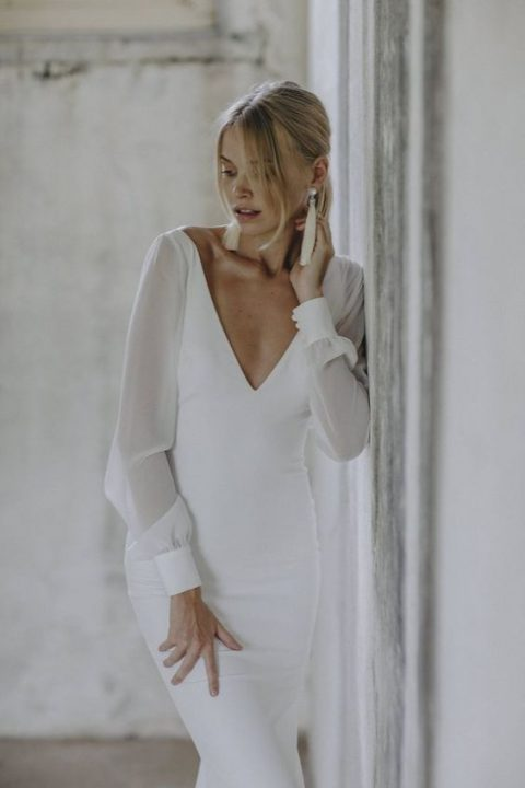 a modern and elegant wedding dress with a fitting silhouette, a plunging neckline, sheer long sleeves and tassel earrings