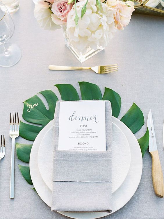 mark each place setting with a large palm leaf to make it stand out and add coloring to the table