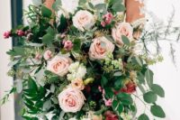 34 a classic oversized wedding bouquet that includes pink roses, greenery, berries and thistles