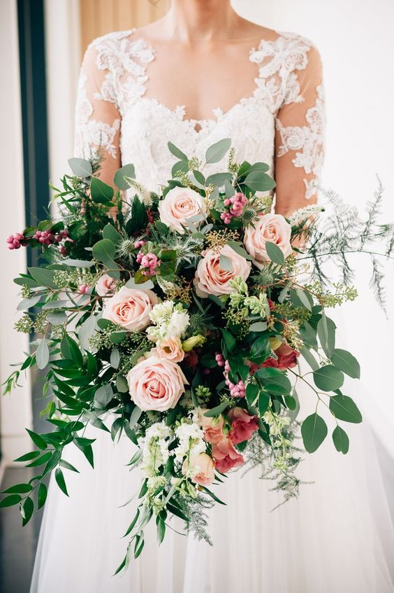 a classic oversized wedding bouquet that includes pink roses, greenery, berries and thistles