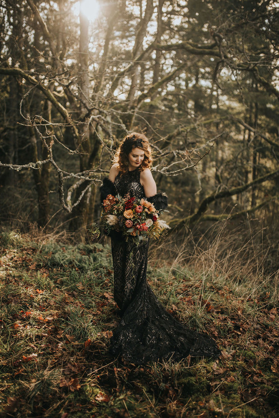 a gorgeous black lace embellished wedding dress with a long train for a Halloween wedding