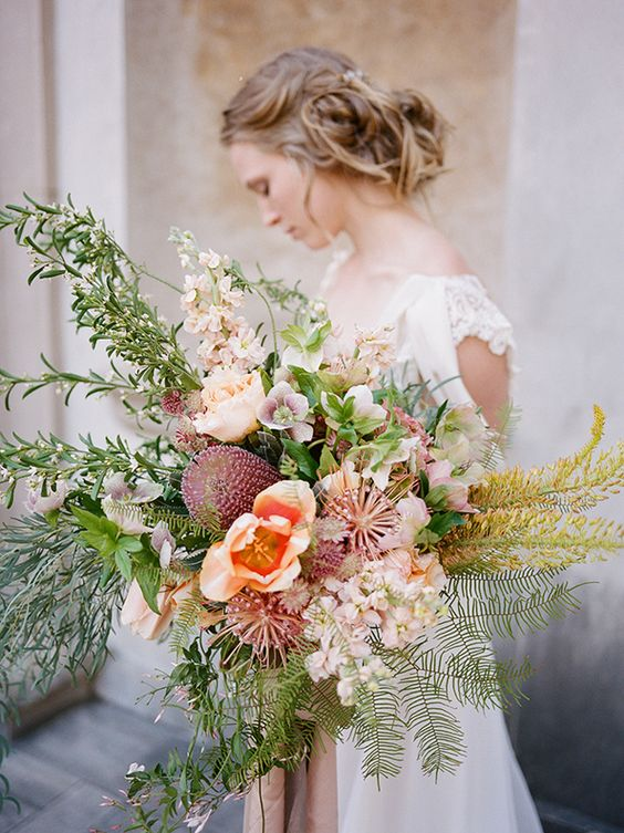 an oversized wedding bouquetin pink shades and lush textural greenery plus yellow herbs
