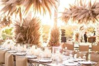 38 a sun-lit wedding venue fully decorated with pampas grass arrangements everywhere