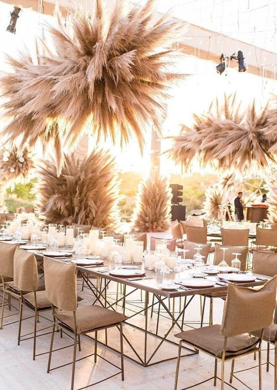 a sun-lit wedding venue fully decorated with pampas grass arrangements everywhere
