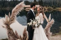 39 a hexagon wedding arch decorated with pampas grass looks very boho and very cool
