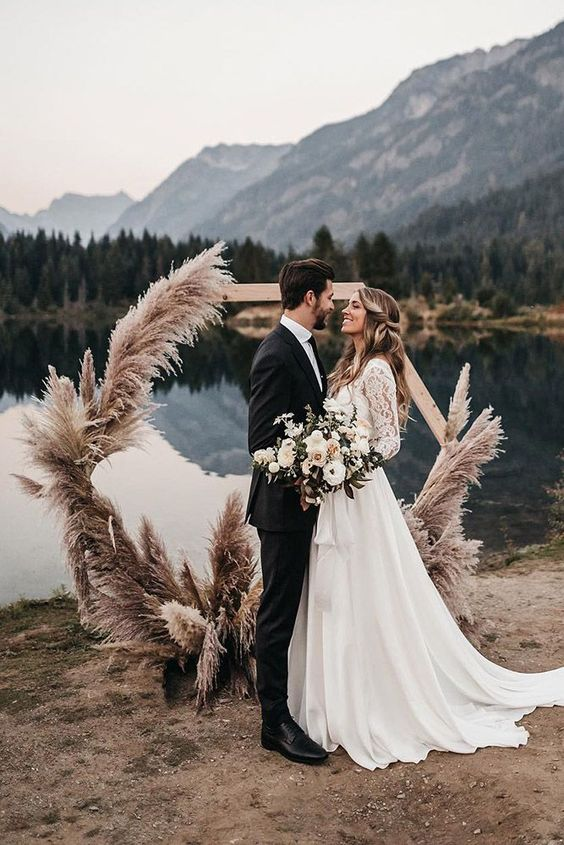 a hexagon wedding arch decorated with pampas grass looks very boho and very cool