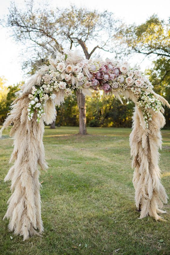 a lush wedding arch covered with pampas grass and blush and pink blooms on top