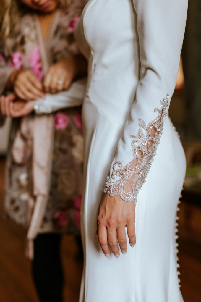 a plain wedding dress with gorgeous cutout, embroidered and embellished sleeves