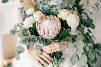 42 a romantic wedding bouquet with eucalyptus, white roses and a single king protea that makes a statement