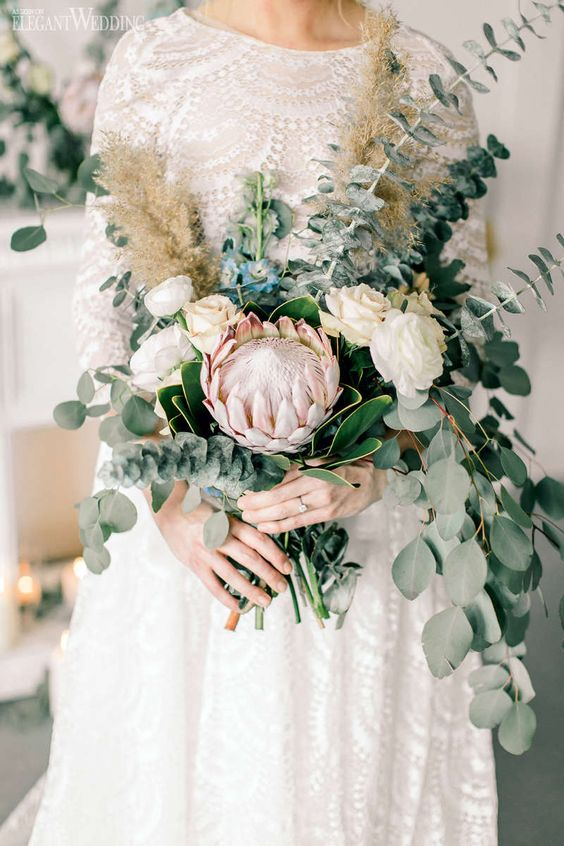 a romantic wedding bouquet with eucalyptus, white roses and a single king protea that makes a statement