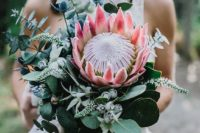 43 a gorgeous bouquet with a king protea, eucalyptus, blue thistles and some pale herbs for a tropical bride