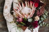 44 a fall boho wedding bouquet with a vertical shape, a king protea, burgundy and plum blooms, herbs and greenery plus a bow