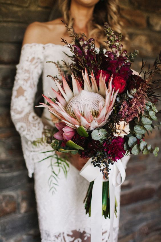 a fall boho wedding bouquet with a vertical shape, a king protea, burgundy and plum blooms, herbs and greenery plus a bow