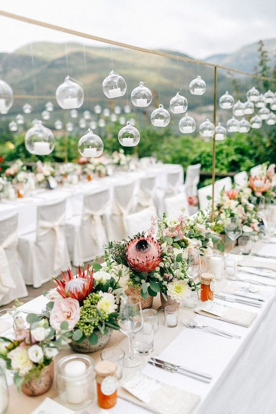 bright wedding centerpieces done with greenery and blush blooms plus king proteas