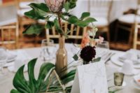 46 a modern wedding centerpiece of tropical leaves, some dark and pastel blooms and a king protea