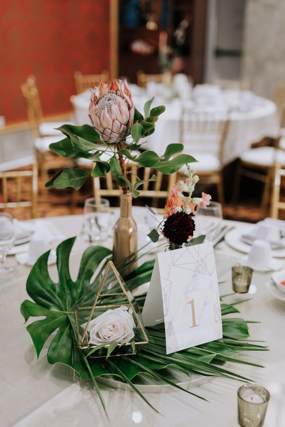a modern wedding centerpiece of tropical leaves, some dark and pastel blooms and a king protea