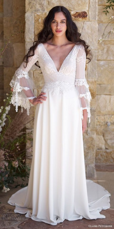 a romantic lace applique bodice wedding gown with a deep V-neckline, bell sleeves with intricate lace detailing