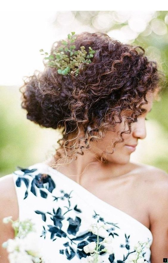 a curly low updo with some curls down and a fresh greenery branch tucked into the hairstyle for a fresh touch