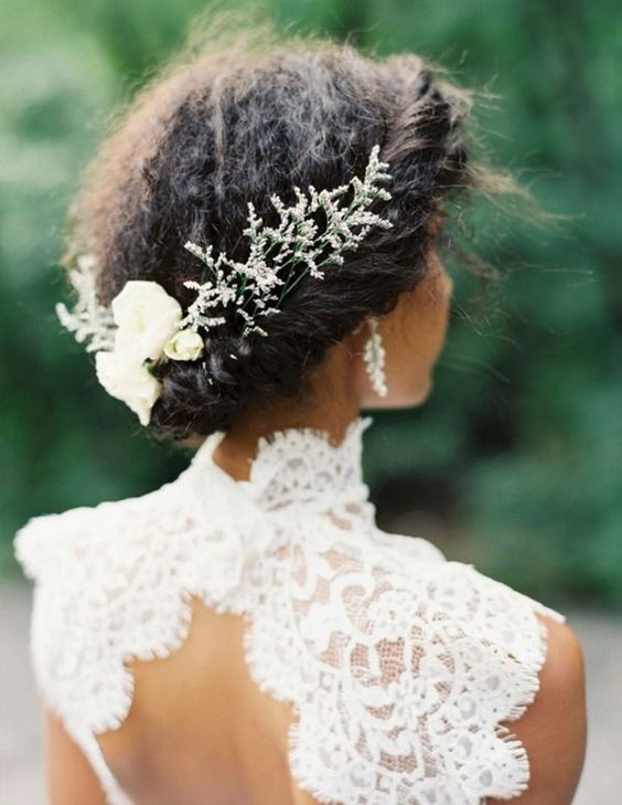 a messy and textural wedding updo with a twisted halo and some greenery and white blooms for an accent