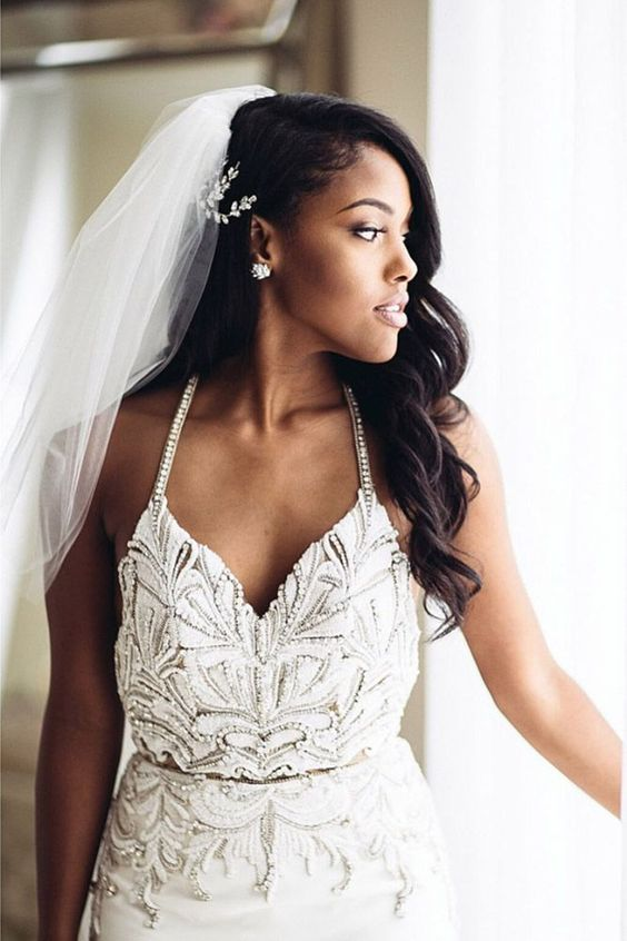 a romantic one side wavy hairstyle with a chic veil and a rhinestone hairpiece looks really cool
