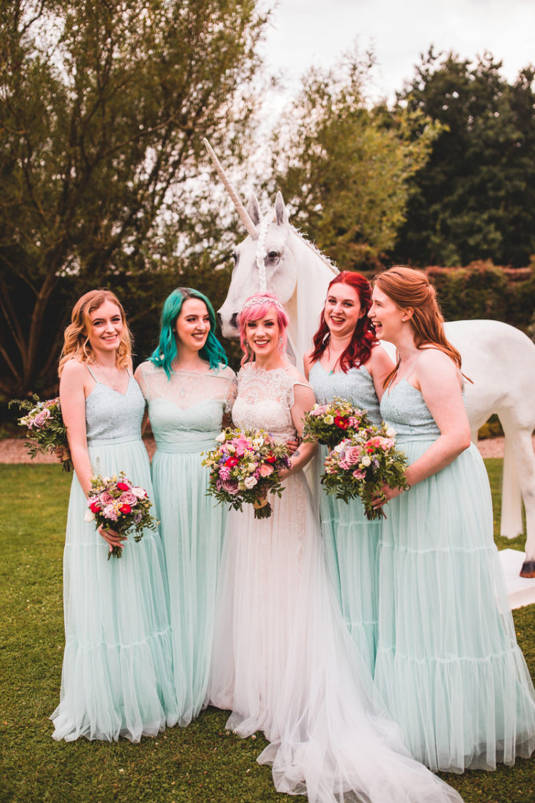 The bride was wearing a lace cap sleeve wedding dress with a train, the bridesmaids were rocking mint green separates and colorful bouquets
