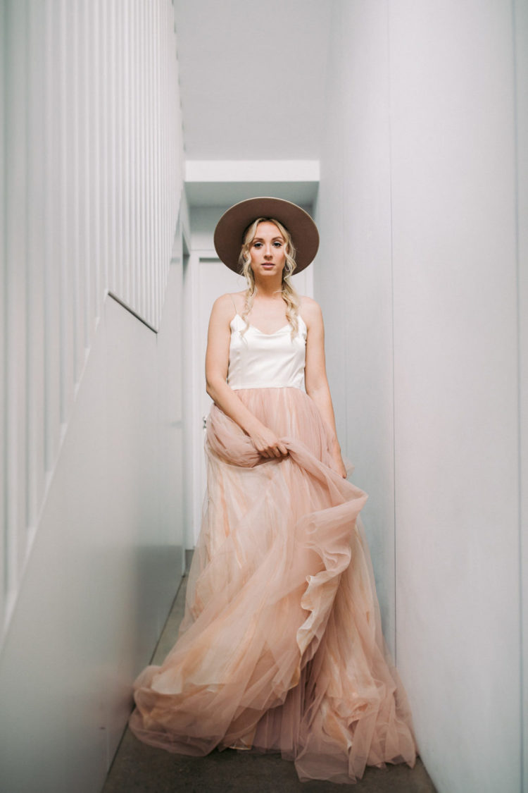 The bride was wearing a spaghetti strap wedding dress with a layered pink skirt and a wide brim hat