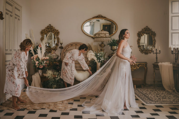 The bride was wearing a white sequin one shoulder wedding dress with a slit, an overskirt and a long train