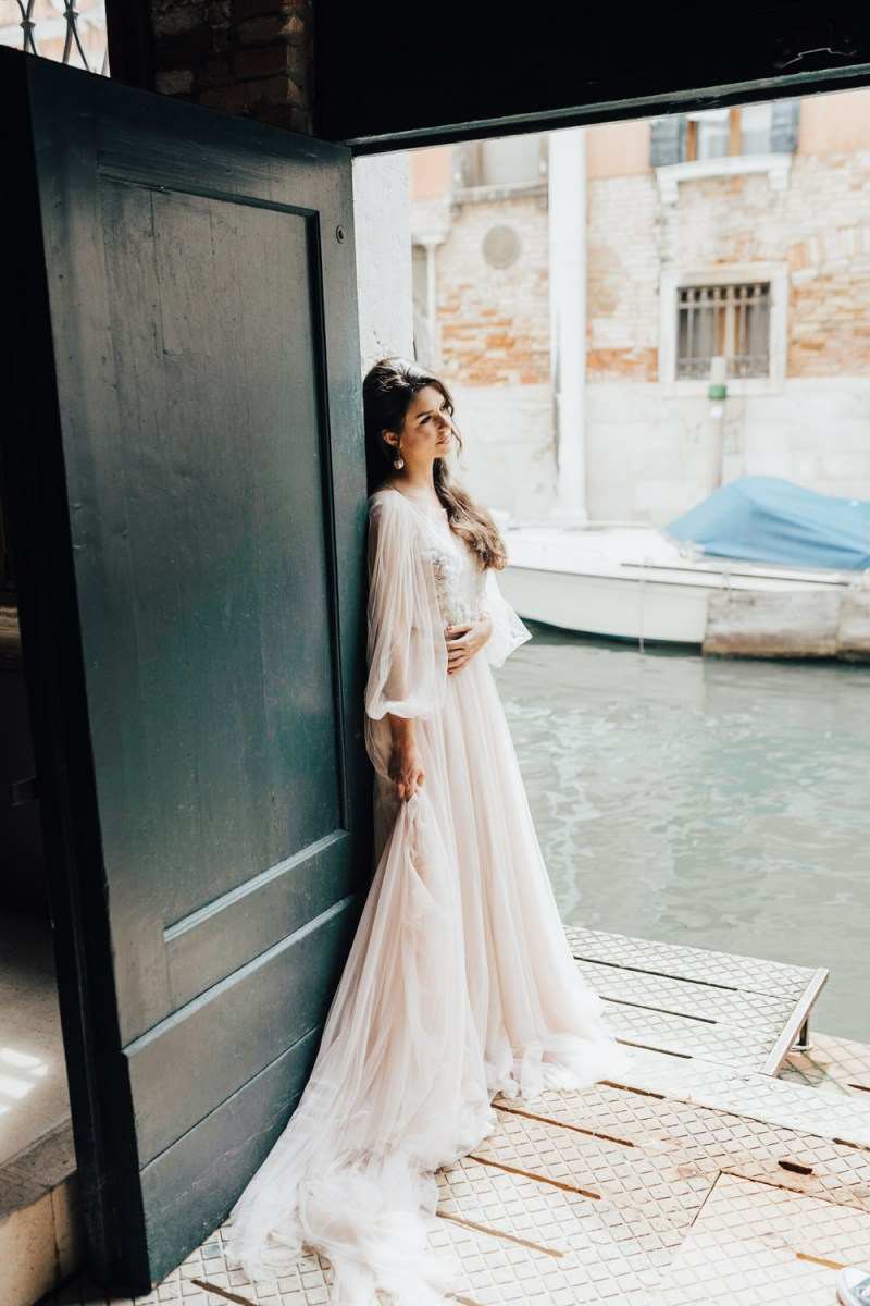 The first wedding dress was a blush one, with flowy sleeves and an embellished bodice plus a train