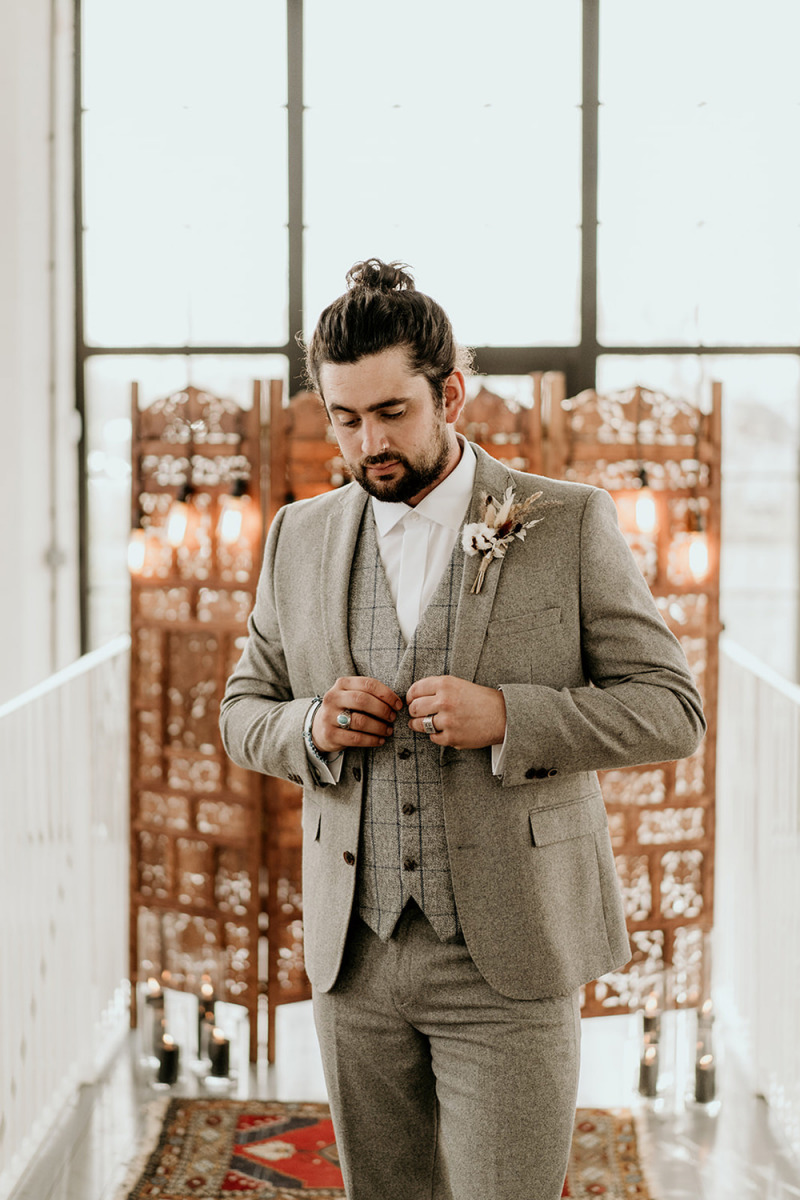 The groom was wearing a grey three piece suit and a trendy top knot