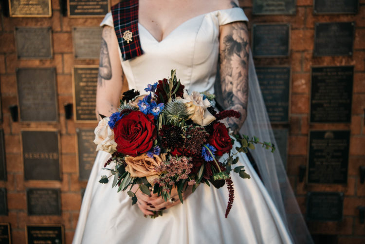 The wedding bouquet was a bold one, with burgundy and blue blooms