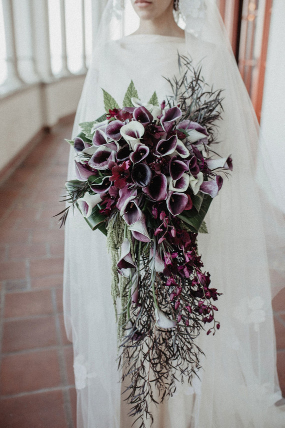 The wedding bouquet was done of purple callas, greenery and it was lush and cascading
