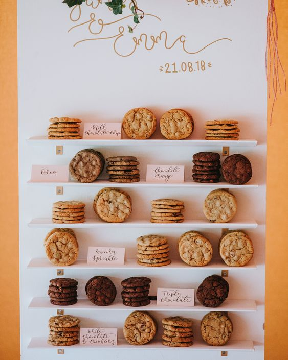 a mini cookie wall with shelves, calligraphy, greenery and various kinds of tasty cookies for a modern wedding