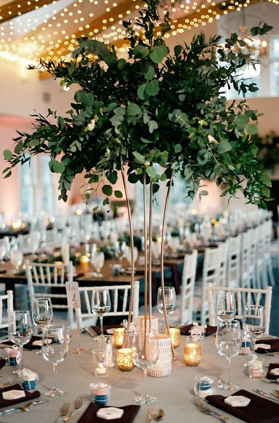 a tall greenery centerpiece is a cool statement idea that won't require much money