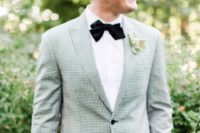 02 a very elegant gentleman wedding look with a checkerboard jacket, black pants and a black velvet bow tie