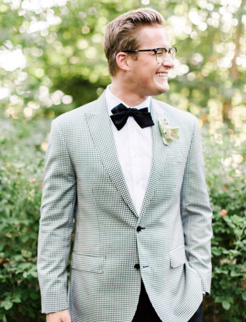 a very elegant gentleman wedding look with a checkerboard jacket, black pants and a black velvet bow tie