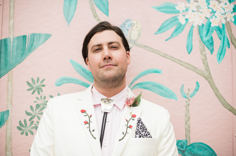 a whimsical groom look with a white suit, a pink shirt, a bolo tie and a leopard handkerchief