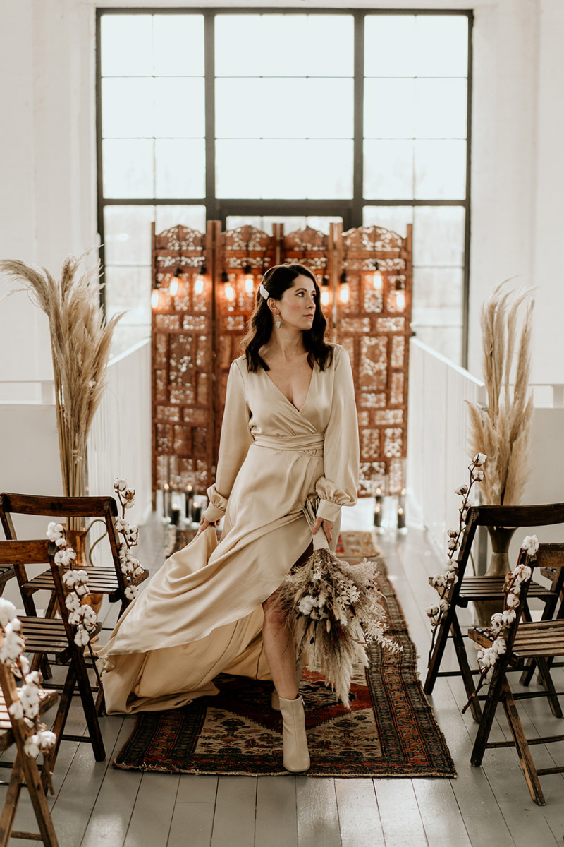 The bride was wearing a neutral silk wrap wedding dress, booties and carrying a chic bouquet