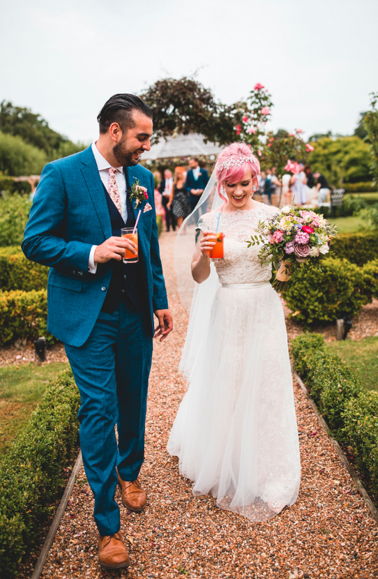 The groom was wearign a bright blue suit with a navy waistcoat and a colorful floral tie