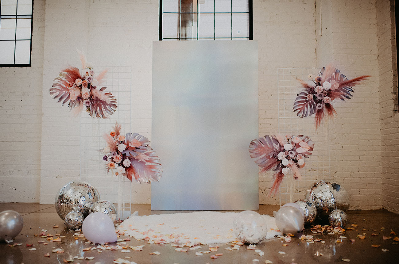 The wedding ceremony is fantastic, with pink palm leaves and blooms, silver disco balls, petals and a holographic backdrop